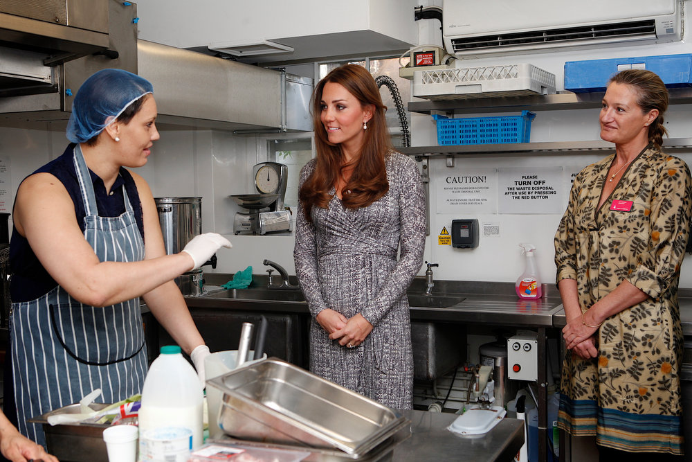 Description of . Catherine, Duchess of Cambridge meets counsellor Lou Kramer (R) and Hope House resident  Sabrina (L) as she visits the kitchens at Hope House residential centre, run by Action on Addiction for recovering addicts on February 19, 2013 in London, England. The Duchess, who is patron of the centre spent over an hour talking to residents at the centre, on her first public engagement since early January. (Photo by Mary Turner - WPA Pool/Getty Images)