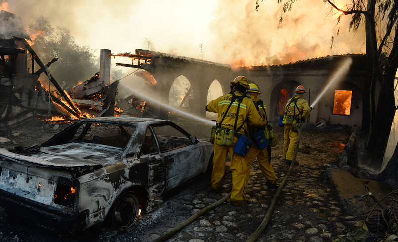 . Firefighters douse the flames  on a house in Glendora Calif., Thursday, Jan. 16, 2014. Nearly 2,000 residents were evacuated and two homes burned in a wildfire that started early Thursday when three people tossed paper into a campfire in the dangerously dry and windy foothills of Southern California\'s San Gabriel Mountains, authorities said.   (AP Photo/The Inland Valley Daily Bulletin, Will Lester)
