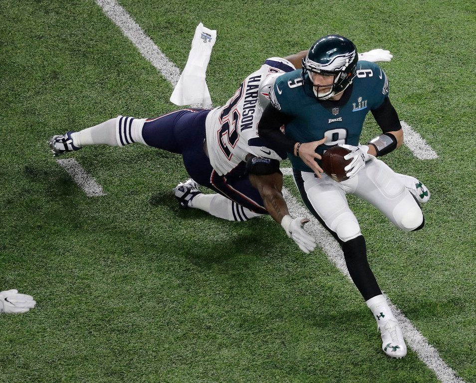 . Philadelphia Eagles quarterback Nick Foles (9) runs around New England Patriots outside linebacker James Harrison during the first half of the NFL Super Bowl 52 football game Sunday, Feb. 4, 2018, in Minneapolis. (AP Photo/Eric Gay)