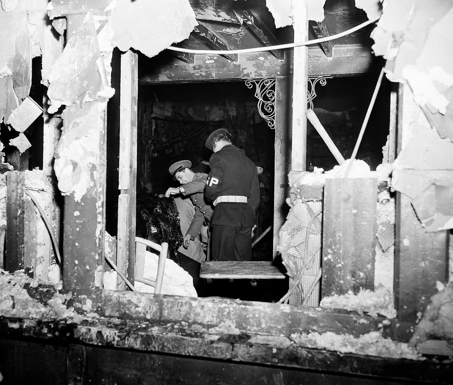 . A soldier and a member of the Navy\'s shore patrol search through charred wreckage at the Cocoanut Grove night club where a disastrous fire caused the deaths of 492 people in the Back Bay section of Boston, Nov. 28, 1942.  (AP Photo)