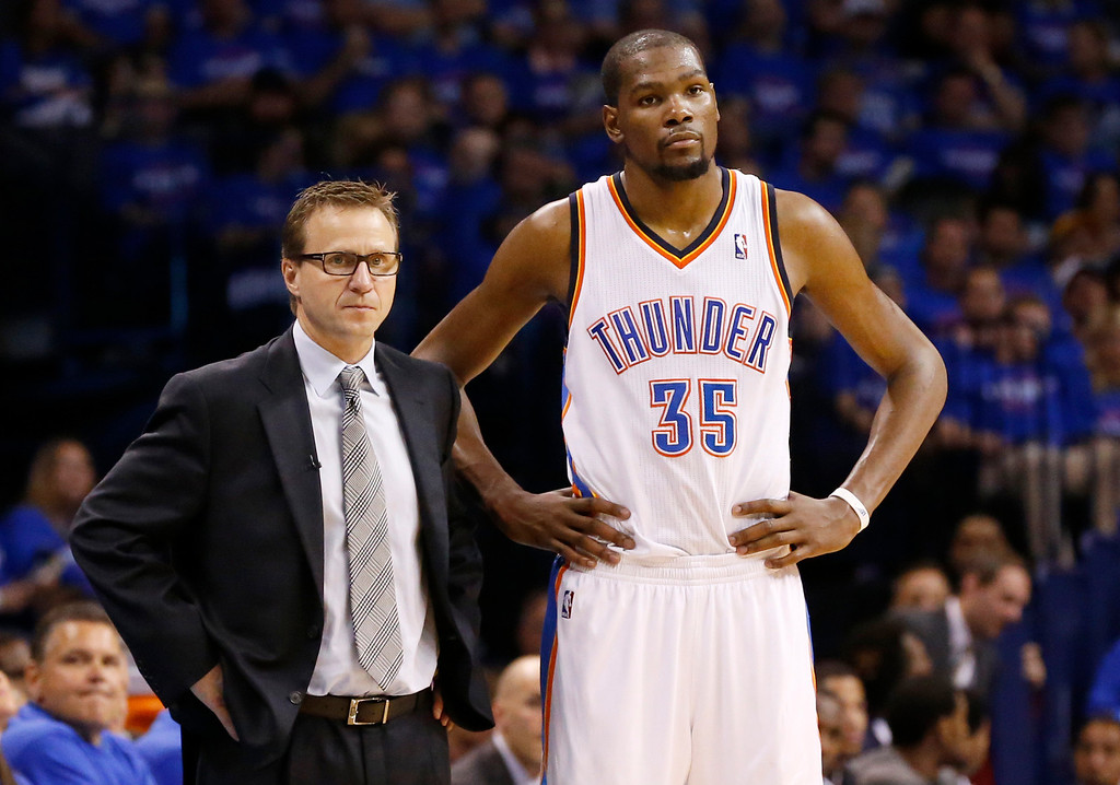 . Oklahoma City Thunder head coach Scott Brooks, left, and forward Kevin Durant, right, watch during a foul shot by the Los Angeles Clippers in the third quarter of Game 1 of the Western Conference semifinal NBA basketball playoff series in Oklahoma City, Monday, May 5, 2014. Los Angeles won 122-105. (AP Photo/Sue Ogrocki)