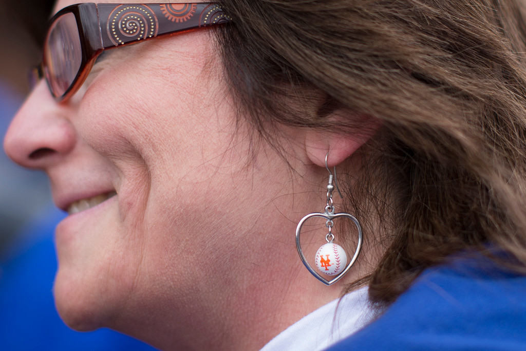 . Teresa Turano, from the Brooklyn borough of New York, wears New York Mets earrings outside Citi Field before an Opening Day baseball game between the Washington Nationals and the Mets, Monday, March 31, 2014, in New York. (AP Photo/John Minchillo)