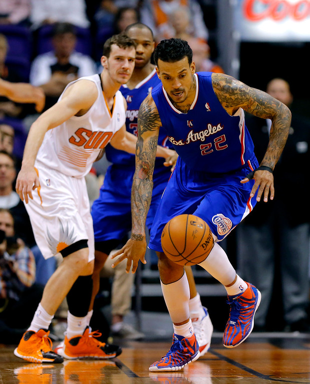 . Los Angeles Clippers forward Matt Barnes (22) chases down the loose ball as Phoenix Suns guard Goran Dragic, Slovenia, looks on during the first half of an NBA basketball game on Wednesday, April 2, 2014, in Phoenix. (AP Photo/Matt York)