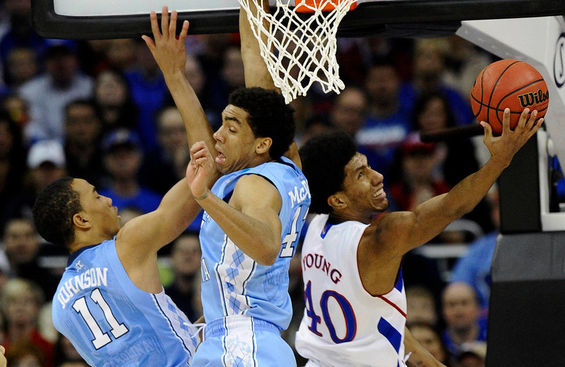 . Kansas Jayhawks forward Kevin Young (R) shoots against North Carolina Tar Heels forward Brice Johnson (11) and forward James Michael McAdoo during the first half of the third round of the NCAA men\'s basketball tournament at the Sprint Center in Kansas City, Missouri March 24, 2013. REUTERS/Dave Kaup