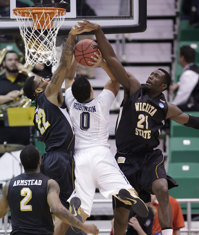 . Wichita State\'s Carl Hall (22) and teammate Ehimen Orukpe (21) block the shot of Pittsburgh\'s James Robinson (0) in the first half during a second-round game in the NCAA college basketball tournament in Salt Lake City Thursday, March 21, 2013. (AP Photo/Rick Bowmer)