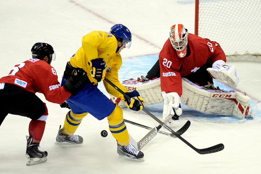 . Sweden\'s Loui Eriksson takes a shot on Switzerland goalie Reto Berra as Yannick Weber defends during the action at Bolshoy Arena. Sochi 2014 Winter Olympics on Friday, February 14, 2014. (Photo by AAron Ontiveroz/The Denver Post)