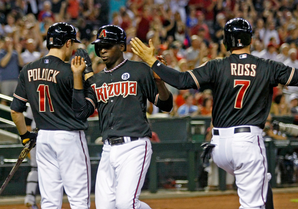 . Arizona Diamondbacks Didi Gregorius (1), middle, celebrates with A.J. Pollock (11), and Cody Ross (7) after all of them score on a Wade Miley double in the second inning during a baseball game against the Colorado Rockies on Saturday, July 6, 2013, in Phoenix. (AP Photo/Rick Scuteri)