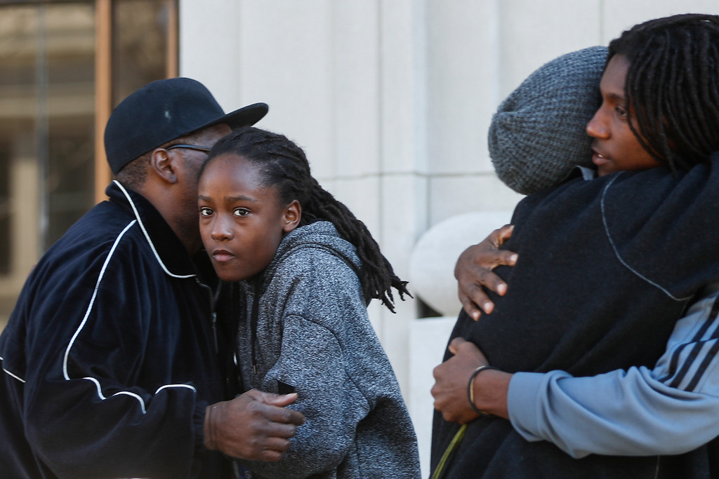 . Family and friends of Sam DuBose embrace outside the Hamilton County Courthouse after a mistrial is declared due to a hung jury in the murder trial against Ray Tensing, Saturday, Nov. 12, 2016, in Cincinnati. Tensing, a white former University of Cincinnati police officer, was charged with murder in the shooting of DuBose, an unarmed black motorist, while on duty during a routine traffic stop on July 19, 2015. (AP Photo/John Minchillo)