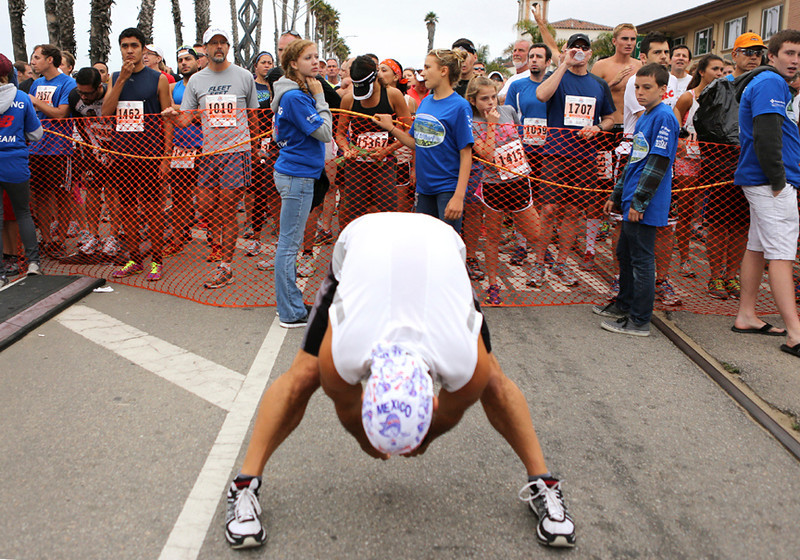 . Runners do some last-minute stretching at the starting line of the Wharf to Wharf race in Santa Cruz on Sunday morning. (Kevin Johnson/Sentinel)