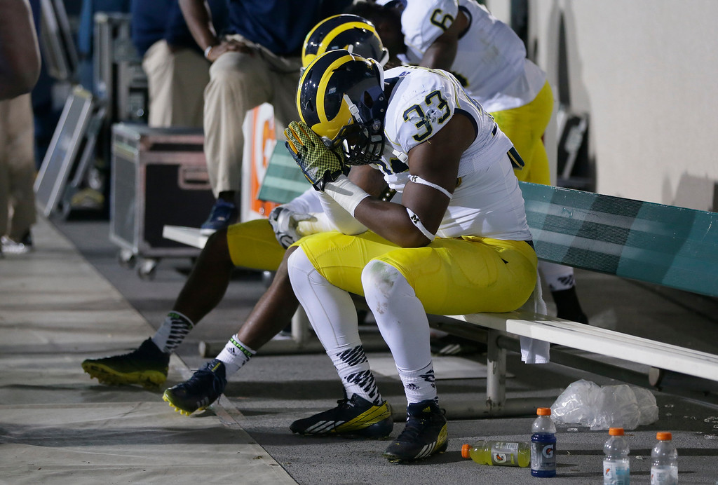 . Michigan defensive end Taco Charlton (33) reflects on the bench during the closing seconds of the second half of an NCAA college football game against Michigan State in East Lansing, Mich., Saturday, Oct. 25, 2014. Michigan State defeated Michigan 35-11. (AP Photo/Carlos Osorio)