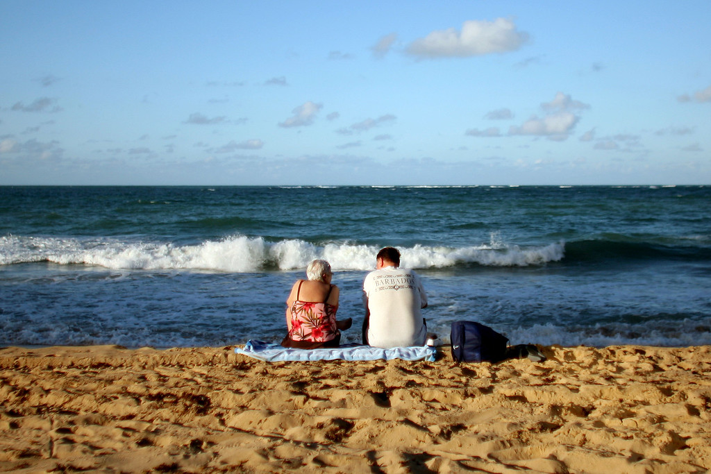 . Two tourists sit in the sand on a beach in San Juan, Puerto Rico, Wednesday Nov. 23, 2011.  (AP Photo/Ricardo Arduengo)