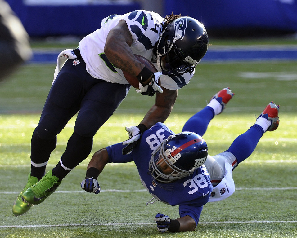 . Seattle Seahawks running back Marshawn Lynch (24) is hit by New York Giants cornerback Trumaine McBride (38) during the first half of an NFL football game on Sunday, Dec. 15, 2013, in East Rutherford, N.J. (AP Photo/Bill Kostroun)