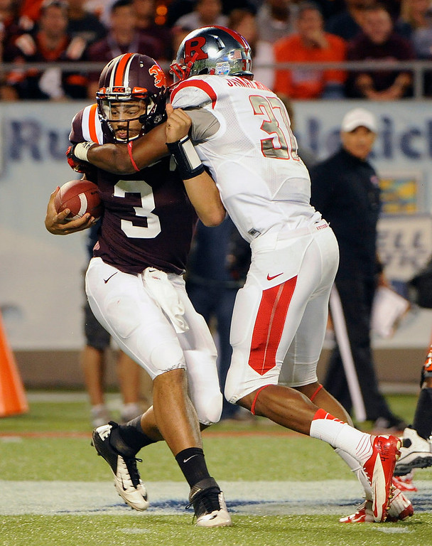 . Virginia Tech quarterback Logan Thomas, left, is sacked for a loss of eight yards by Rutgers linebacker Jamal Merrell during the first quarter of an NCAA college football Russell Athletic Bowl game on Friday, Dec. 28, 2012, in Orlando, Fla. (AP Photo/Brian Blanco)