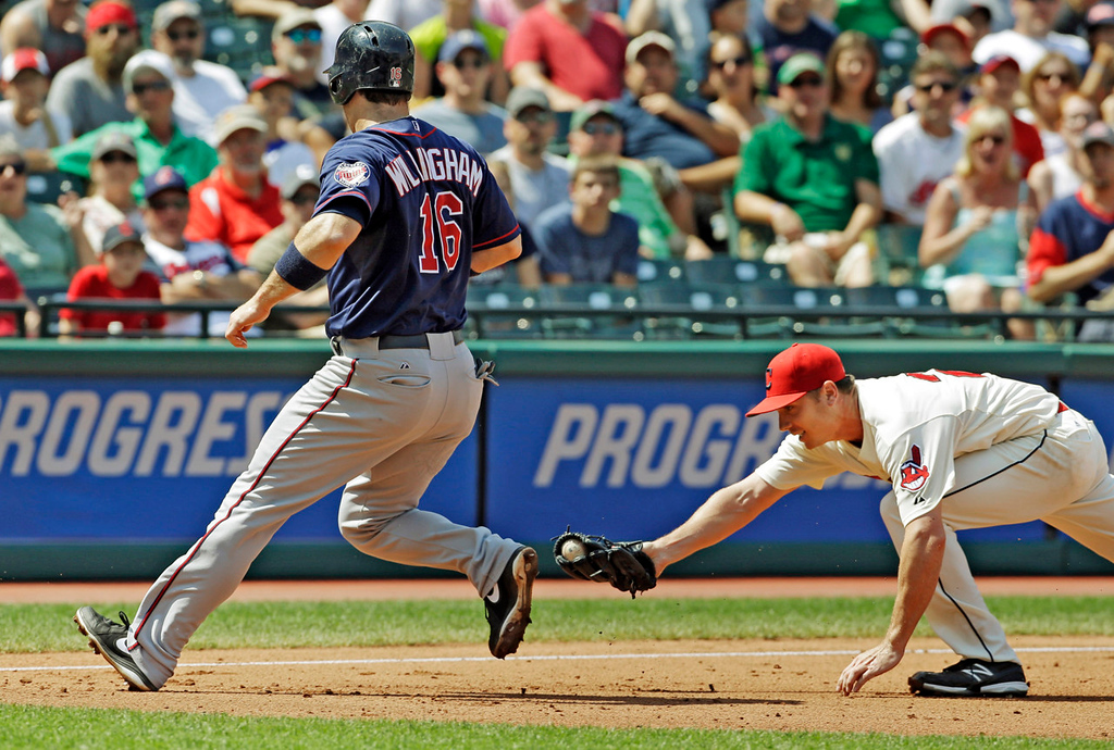 . Minnesota\'s Josh Willingham, left, eludes the tag by Indians starter Scott Kazmir to reach third after being caught in a rundown in the fourth inning. (AP Photo/Mark Duncan)