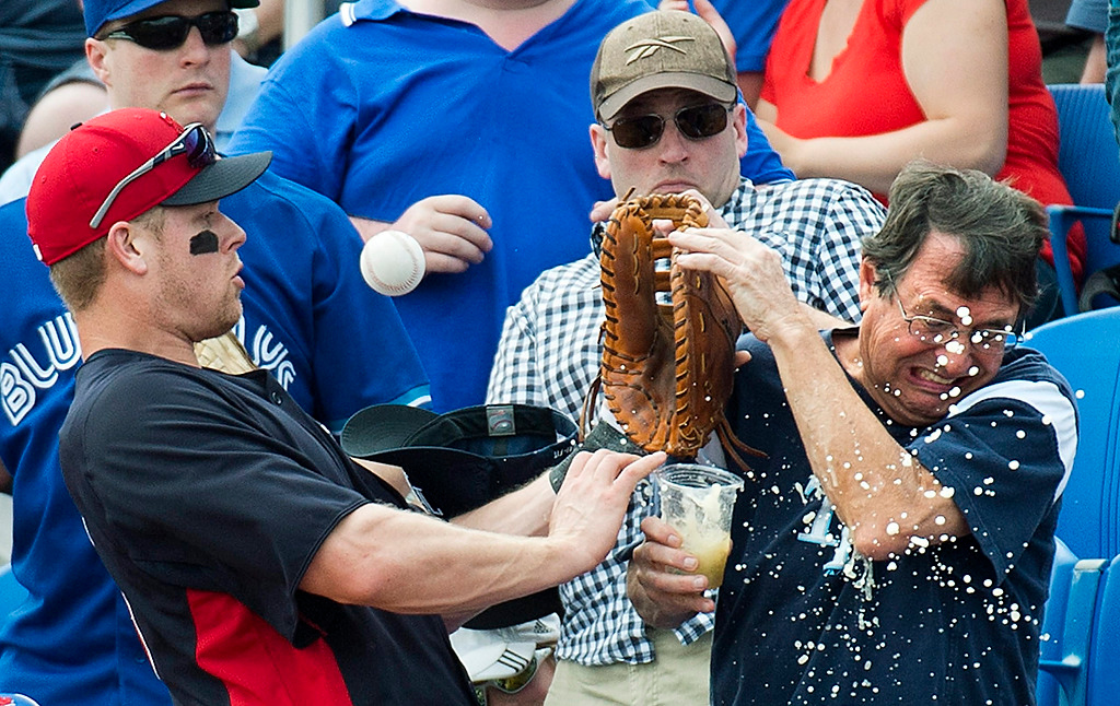 . Minnesota Twins first baseman Justin Morneau, left, runs into a fan and spills his drink while chasing a foul ball against the Toronto Blue Jays during the first inning of an exhibition game in Dunedin, Fla., on Tuesday, Feb. 26, 2013. (AP Photo/The Canadian Press, Nathan Denette)