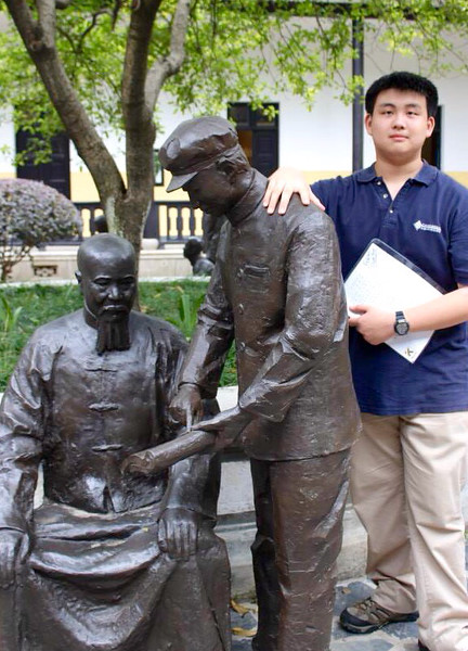 A Concordia International School Shanghai student posing with statues at Hunan First Normal School (a school where Mao Zedong once studied).