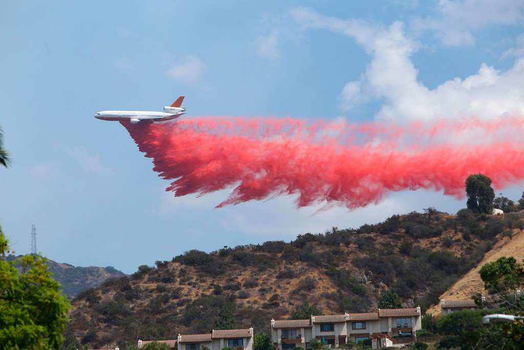 ". A DC-10 Tanker Air Carrier drops Phos-Chek retardant across a ridge while fighting the ""LaTuna Fire\"" on the hillside in Burbank, Calif., Saturday, Sept. 2, 2017. The DC-10 delivers some 11,600 gallons of retardant per load. Several hundred firefighters worked to contain a blaze that chewed through brush-covered mountains, prompting evacuation orders for homes in Los Angeles, Burbank and Glendale. (Matt Hartman via AP)"