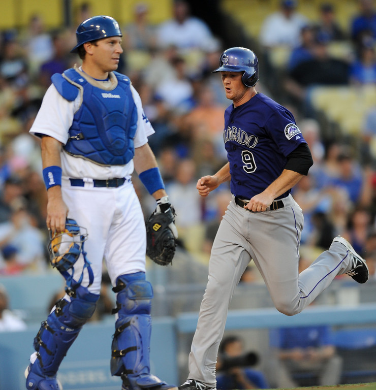 . The Rockies\' DJ LeMahieu scores from second on a hit by Wilin Rosario as Dodgers catcher A.J. Ellis stands at home, Friday, July 12, 2013, at Dodger Stadium. (Michael Owen Baker/Staff Photographer)