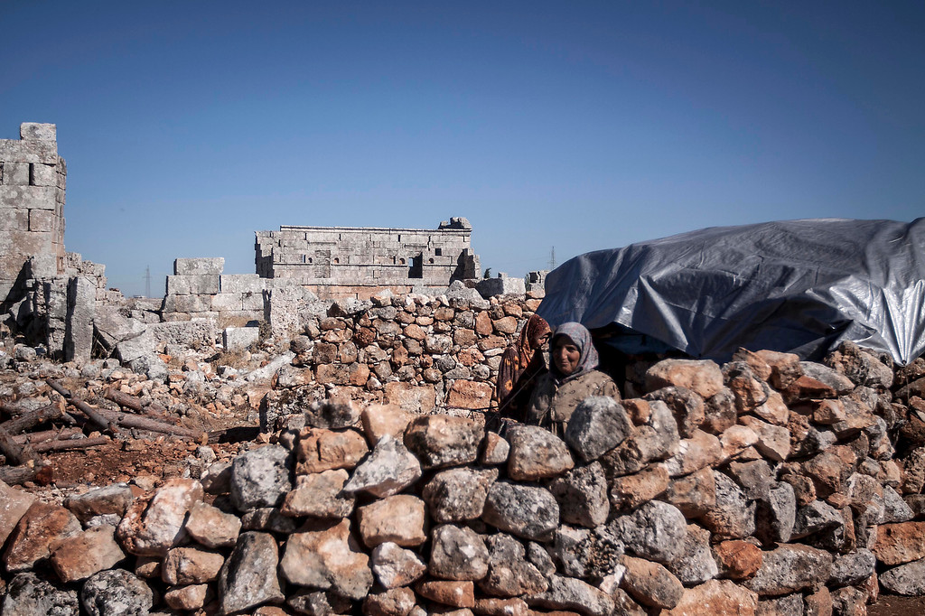 . In this Friday, Sept. 27, 2013 photo, displaced Syrian women walk in the yard of their family stone house near Kafer Rouma, in ancient ruins used as temporary shelter by those families who have fled from the heavy fighting and shelling in the Idlib province countryside of Syria.(AP Photo)