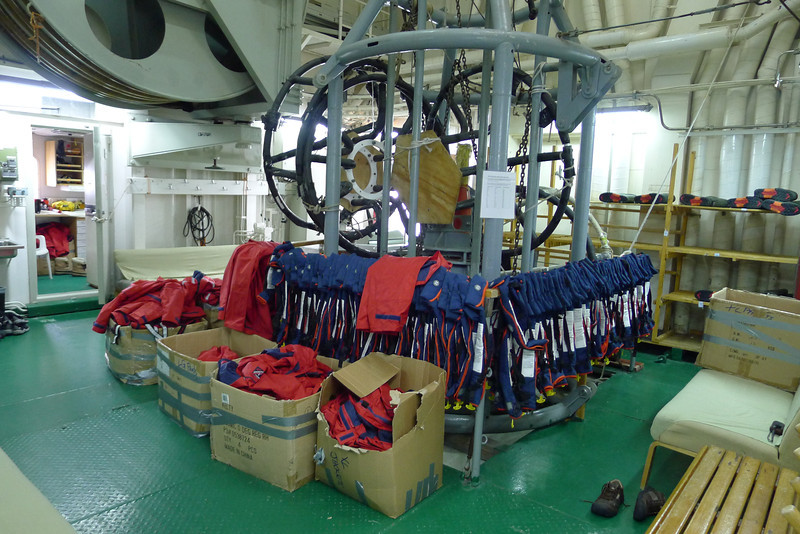 """Antarctica - Jan 2013 - Sergey Vavilov Circle Trip, The One Ocean Expedition  Mud room with jackets, life jackets and boots. Here is where you exit and enter for Zodiac & shore excursions.  This is an interesting area of the ship as during it """"scientific research"""" days, instruments could be lowered directly into the sea from this room, the large wheel (left) would contain the cables etc to do the lowering of the equipment.  When in this room you can still hear the sloshing of the water below.  Apparently the Sergey Vavilov and Loffe would act work together over large distances during these activities."""