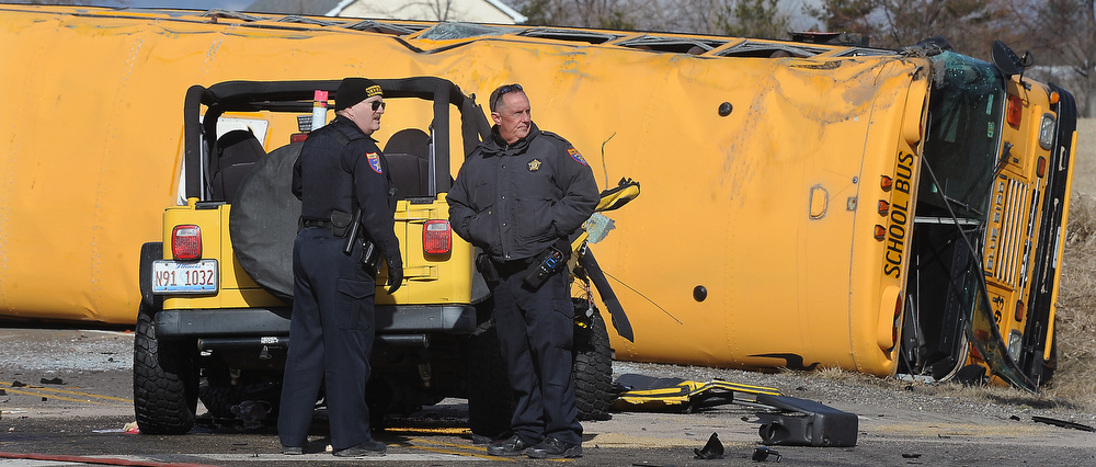. Emergency personnel stand at the scene where a school bus carrying around two dozen elementary school children overturned, Friday, April 5, 2013, near Wadsworth, Ill. Authorities say one person has died and more than three dozen people are injured. (AP Photo/The Kenosha News, Bill Siel)
