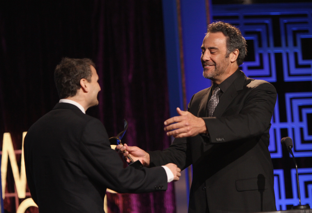 Description of . Actor Brad Garrett (R) presents an award onstage at the 2013 WGAw Writers Guild Awards at JW Marriott Los Angeles at L.A. LIVE on February 17, 2013 in Los Angeles, California.  (Photo by Maury Phillips/Getty Images for WGAw)