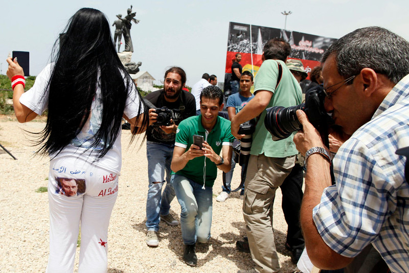 . An activist shows photographers a picture of Syrian President Bashar al-Assad on the seat of her pants during an anti-Hezbollah protest in Beirut June 9, 2013. A Lebanese protester was killed outside the Iranian embassy in Beirut on Sunday after gunmen from the Iranian-backed Shi\'ite militia Hezbollah opened fire when anti-Hezbollah Shi\'ite demonstrators approached, witnesses and officials said.           REUTERS/ Jamal Saidi