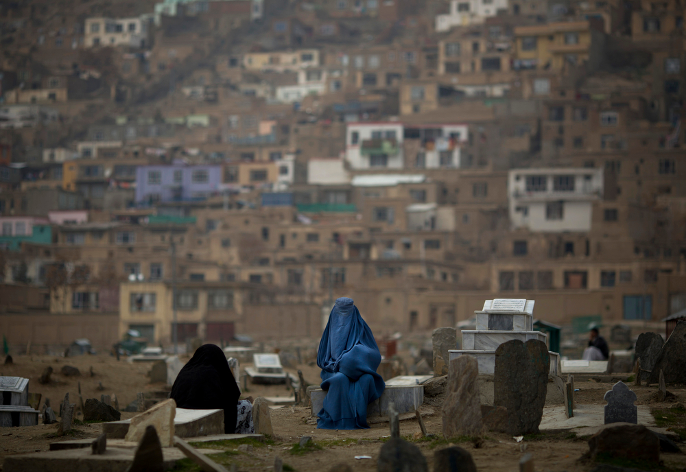 . Afghan women chat at a cemetery in the center of Kabul, Afghanistan, Friday, March 7, 2014. On the eve of the International Women\'s Day 2014, Afghanistan has been named \'the worst place in the world to be a woman.\' (AP Photo/Anja Niedringhaus)