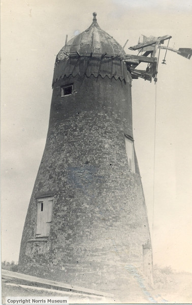 """PH/SPALD/38: Spaldwick Mill:  brick-built tower mill with ogee wooden cap, sails missing and fantail broken.  Three doors and a window in the building (written on the back """"Spaldwick Mill 1922""""). Provided by the Norris Museum"""