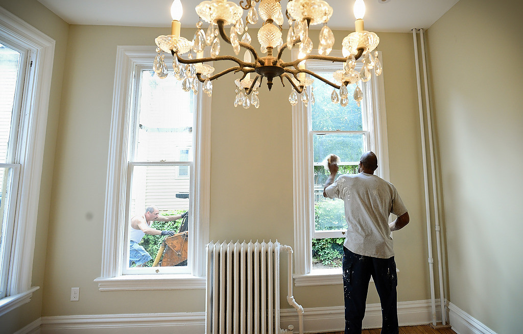 ". Construction worker Darrin Brown cleans windows in a remodeled home at 326 Maria Ave., just down the street from the Wardlaws�. The home, built in 1879, is categorized as ""pivotal\"" to the district�s revitalization. (Pioneer Press: Ben Garvin)"