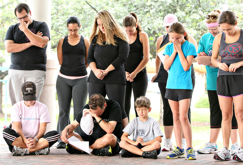 071412 - DELRAY BEACH - Mission pastor John O'Brien (not pictured) leads the members of The Avenue Church congregation in prayer to kick off its physical fitness ministry.  Starting Saturday, July 14th, The Avenue Church launched it's weekly fitness training at Delray Oceanfront Park. The exercise portion of the class is led by Peter Jacobsen, Certified Personal Trainer and marathoner. Photo by Tim Stepien