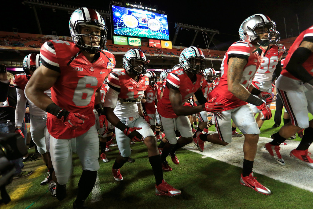 . MIAMI GARDENS, FL - JANUARY 03: The Ohio State Buckeyes run onto the field during warm ups prior to the Discover Orange Bowl against the Clemson Tigers at Sun Life Stadium on January 3, 2014 in Miami Gardens, Florida.  (Photo by Chris Trotman/Getty Images)