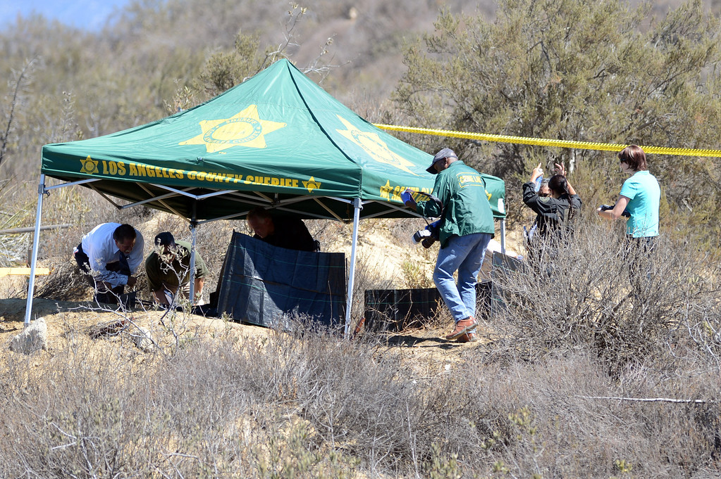 . Investigators work at the location where a burned body was found on Wednesday, Sept. 4, 2013, on Lake Hughes Road, a few miles east of the Golden State (5) Freeway and just south of Castaic Lake. (Hans Gutknecht/Los Angeles Daily News)