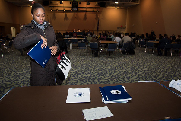 030117  Wesley Bunnell   Staff  CCSU held an informative panel titled Uncertainty around Immigration Law on March 1. Masters student Diana-Kay Walters takes an informational packet for immigrants at a back table set up for guests.