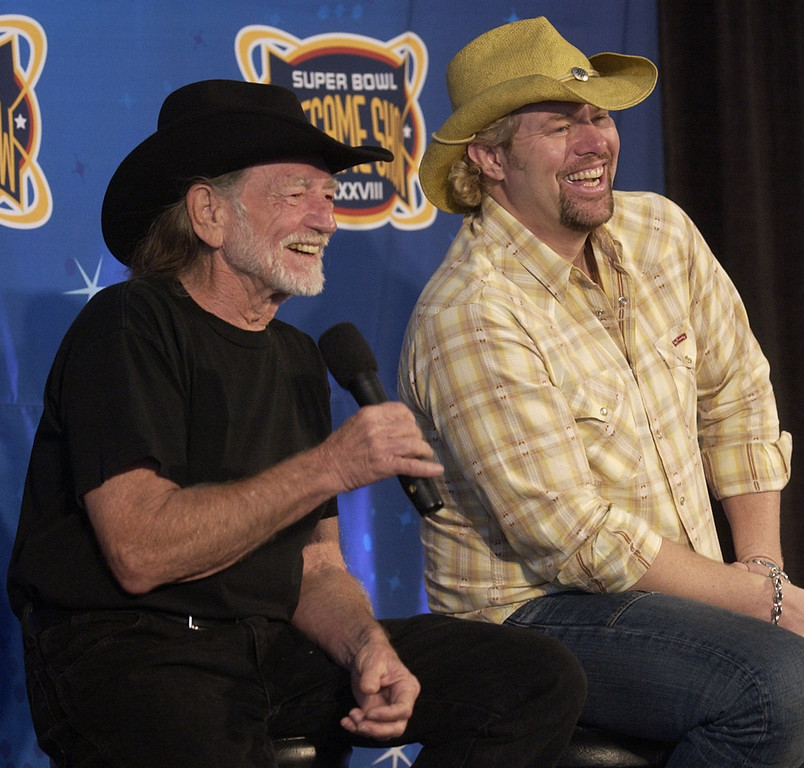 . Country singers Willie Nelson, left, and Toby Keith share a laugh at a press conference in Houston touting the pre-game show for Super Bowl XXXVIII on Friday, Jan. 30, 2004. (AP Photo/Amy Sancetta)