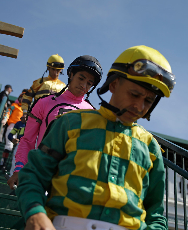 . Jockeys walk into the paddock before a race before the 140th running of the Kentucky Derby horse race at Churchill Downs Saturday, May 3, 2014, in Louisville, Ky. (AP Photo/David Goldman)