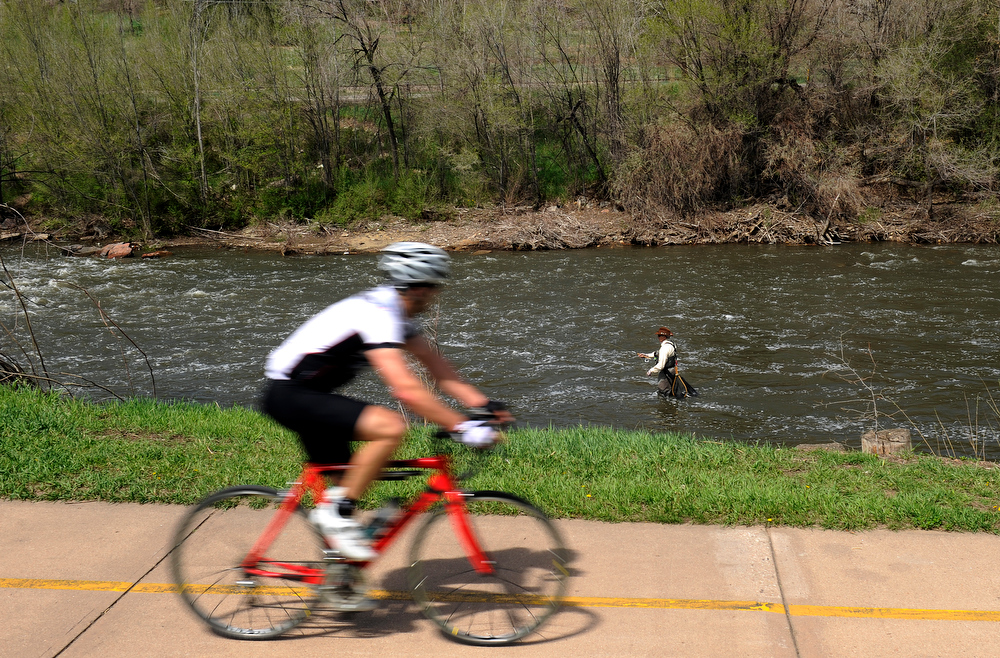 . Urban fishing on Monday, May 13, 2013 along the South Platte River in Denver as a cyclist passes John Davenport.    Photo By Cyrus McCrimmon/The Denver Post)