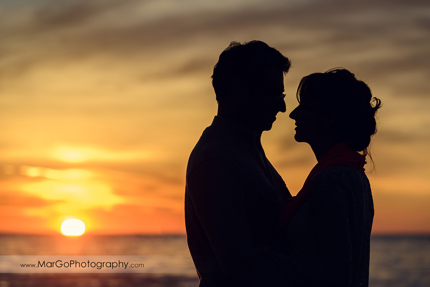 silhouette of man and woman looking at each other during sunset engagement session at San Francisco Baker Beach