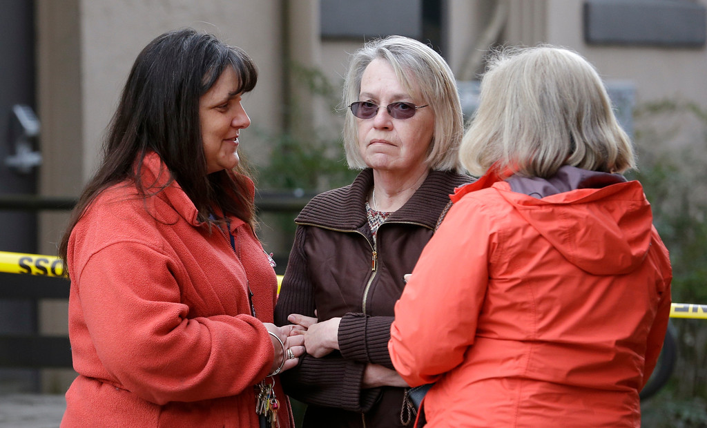 . Barbara Welsh, center, whose husband is missing in a deadly mudslide, stands with relatives Monday, March 24, 2014, in Arlington, Wash.   (AP Photo/Elaine Thompson)