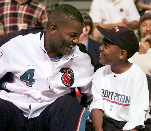 . Detroit Pistons\' Joe Dumars, left, shares a moment with his son Jordan before their game against the Philadelphia 76ers Sunday, May 2, 1999, in Auburn Hills, Mich. Dumars, who is retiring after this season, is playing his last regular season game at The Palace. (AP Photo/Duane Burleson)
