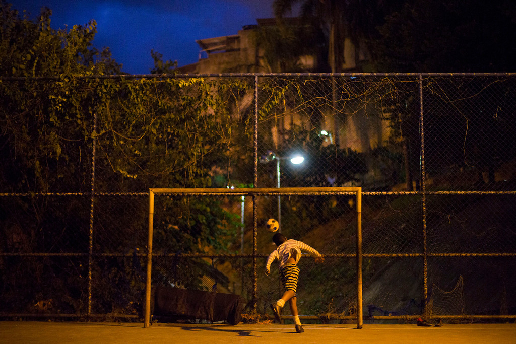 . In this Monday, June 2, 2014 photo, a youth tries to block a ball during a soccer game in the Mangueira slum of Rio de Janeiro, Brazil. Less than half a kilometer separates the slum from Maracana stadium, but slum residents will be following the World Cup on television due to the expense. (AP Photo/Leo Correa)