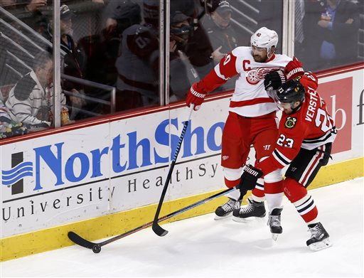 . Detroit Red Wings left wing Henrik Zetterberg (40) and Chicago Blackhawks right wing Kris Versteeg battle for the puck during the first period of an NHL hockey game Wednesday, Feb. 18, 2015, in Chicago. (AP Photo/Charles Rex Arbogast)