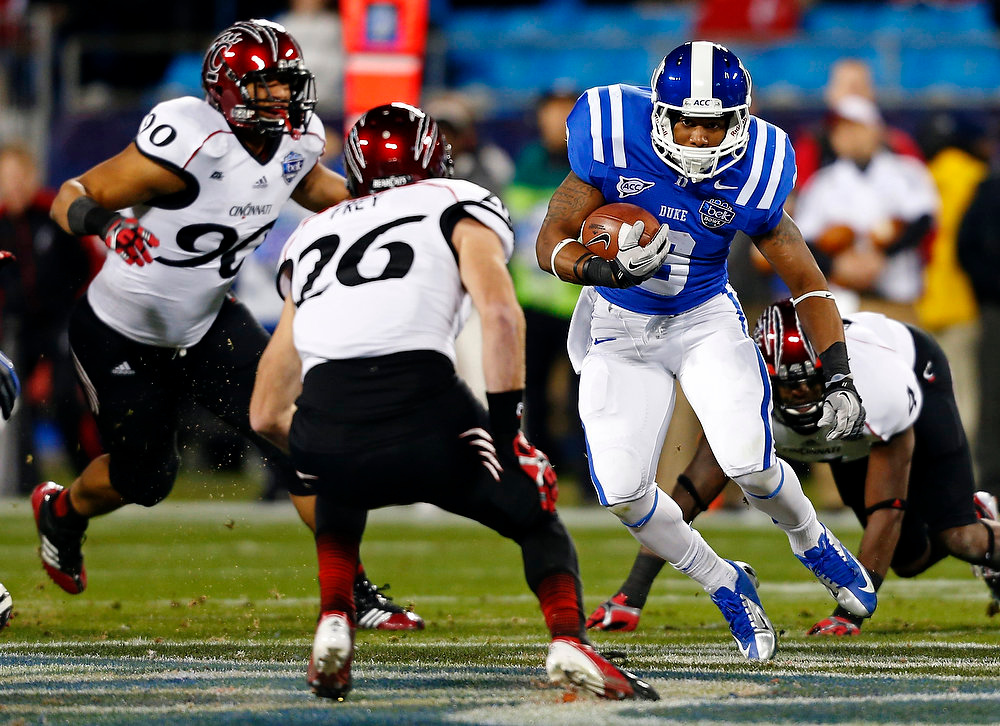 . Duke\'s Josh Snead (9) runs as Cincinnati\'s Drew Frey (26) and Camaron Beard (90) chase during the first half of the Belk Bowl NCAA college football game in Charlotte, N.C., Thursday, Dec. 27, 2012. (AP Photo/Chuck Burton)