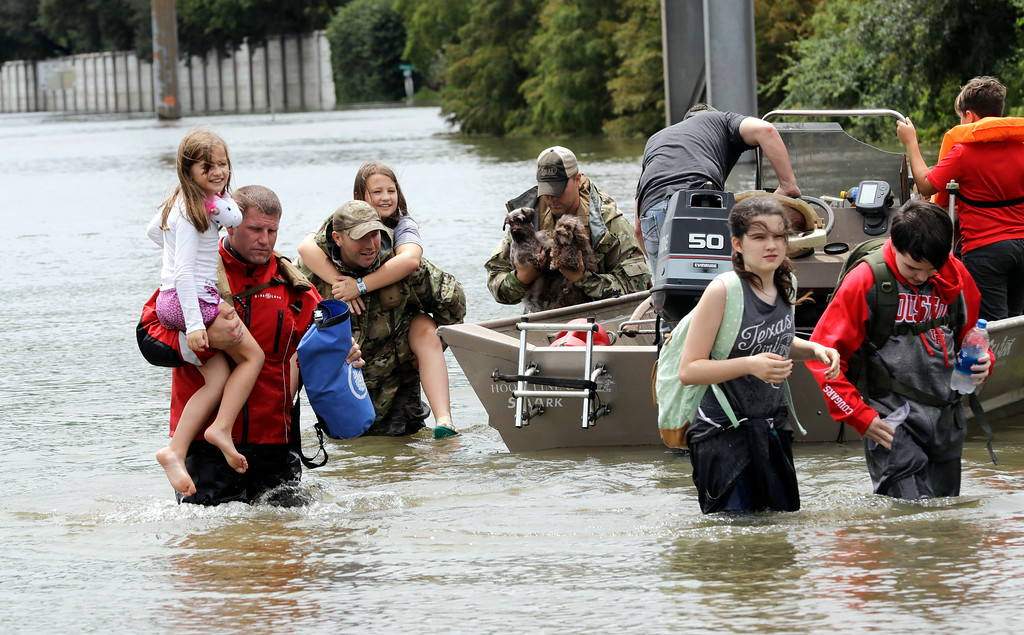 . Residents are rescued from their homes surrounded by floodwaters from Tropical Storm Harvey Sunday, Aug. 27, 2017, in Houston, Texas. (AP Photo/David J. Phillip)