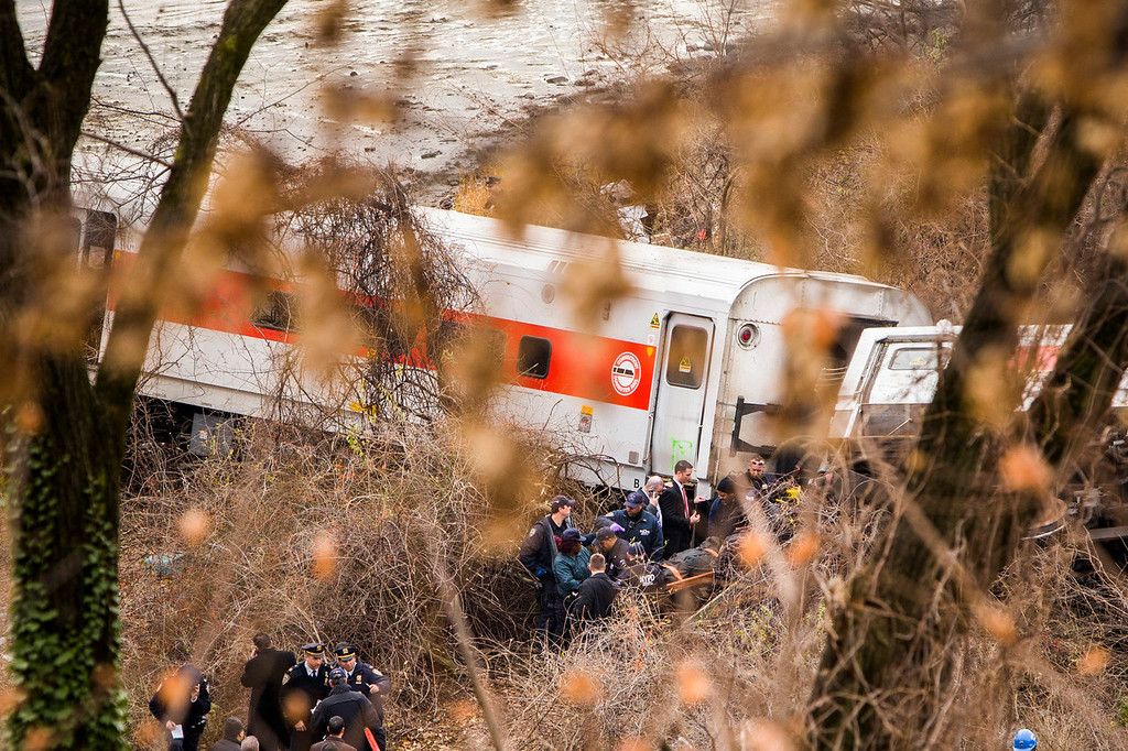 . Emergency workers remove a dead body from the wreckage after a Metro-North commuter train derailed just north of the Spuyten Duyvil station December 1, 2013 in the Bronx borough of New York City. Multiple injuries and at least 4 deaths were reported after the seven car train left the tracks as it was heading to Grand Central Terminal along the Hudson River line.  (Photo by Christopher Gregory/Getty Images)