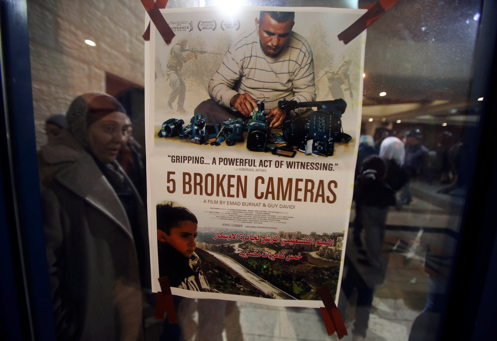". A poster for the Oscar-nominated documentary ""5 Broken Cameras\"" is displayed at a theatre in the West Bank city of Ramallah January 28, 2013. The documentary screened for Palestinians for the first time on Monday, leaving locals hopeful that their struggle with Israel for land and statehood will gain a global audience. The low-cost film is based on five years of amateur camera work by journalist Emad Burnat as he documented weekly protests against land seizures by Israeli forces and Jewish settlers in his village of Bil\'in in the occupied West Bank. Picture taken January 28, 2013. REUTERS/Mohamad Torokman"
