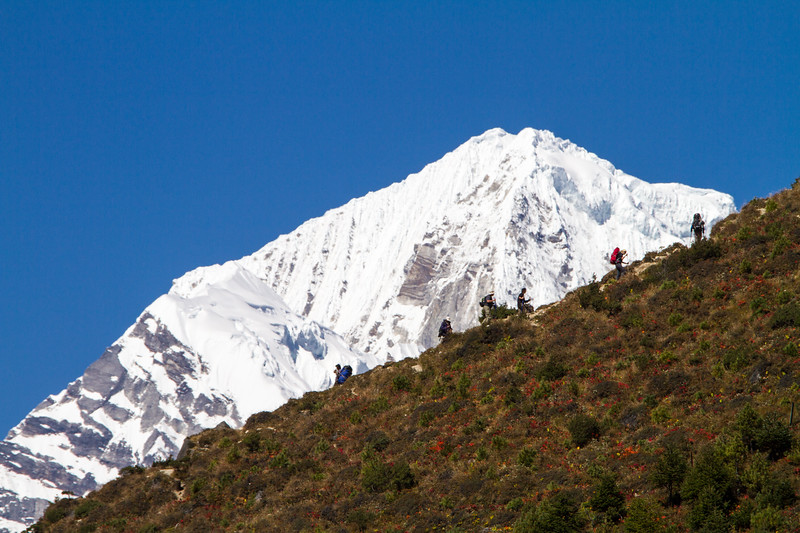 Trekkers in Nepal's Himalayas are seen along an uphill ridgeline with a snow capped peak in the background