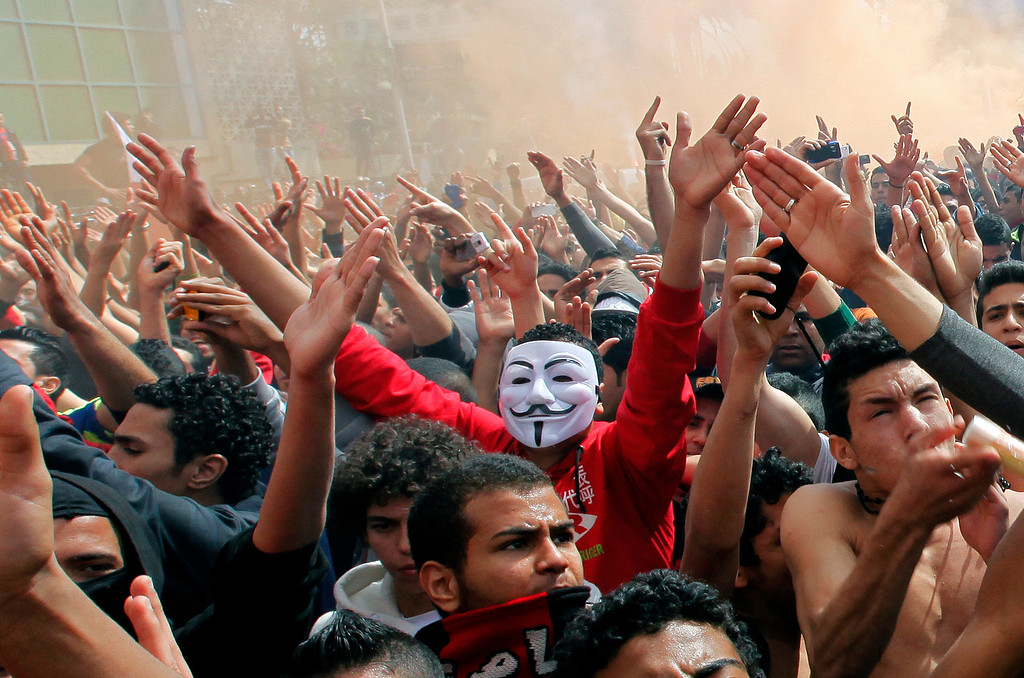 . An Egyptian soccer fans of the Al-Ahly club wearing a Guy Fawkes mask shouts shouts slogans in front of the club in Cairo, Egypt, Saturday, March 9, 2013.(AP Photo/Amr Nabil)