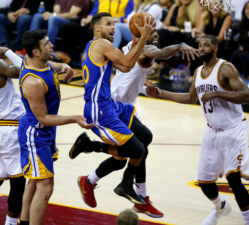 . Golden State Warriors guard Stephen Curry (30) drives on Cleveland Cavaliers guard Kyrie Irving, center rear, during the second half of Game 4 of basketball\'s NBA Finals in Cleveland, Friday, June 9, 2017. (AP Photo/Ron Schwane)