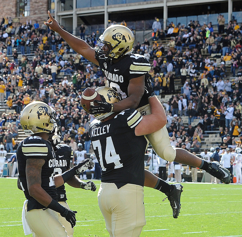 . Colorado\'s Michael Adkins II  is picked up by Alex Kelley after scoring his fourth touchdown against Charleston Southern during an NCAA college football game Saturday. Oct. 19, 2013, in Boulder, Colo. (AP Photo/The Daily Camera, Cliff Grassmick)